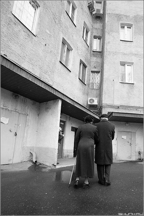 Вдвоем - пара пожилая чёрнобелые он она здание двор улица фото фотосайт