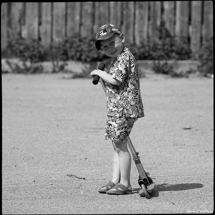 Мальчик - деревня мальчик самокат 2009 забор чёрнобелое среднийформат фото фотосайт