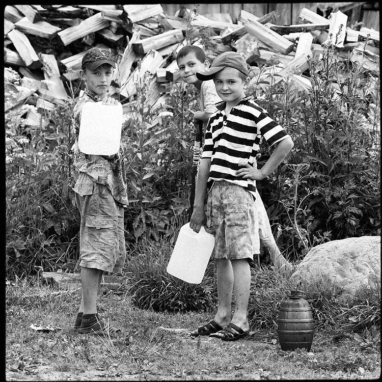 На колонке - вода труба дети канистры чёрнобелые деревня фото фотосайт
